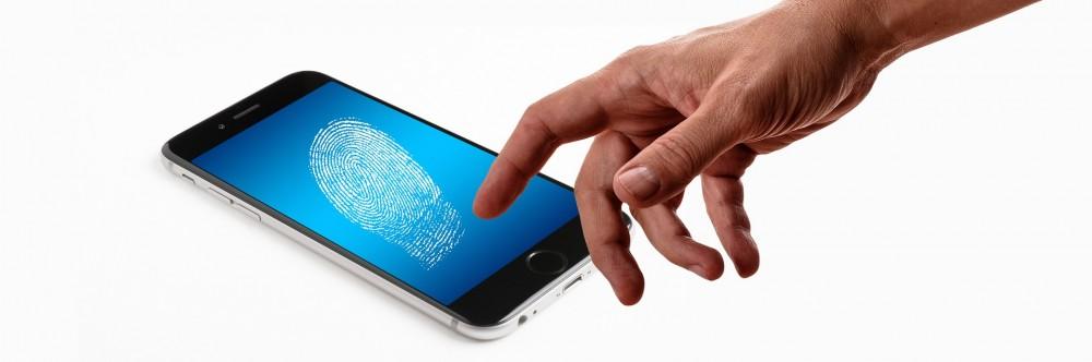 Un dedo toca un móvil para validar la huella dactilar