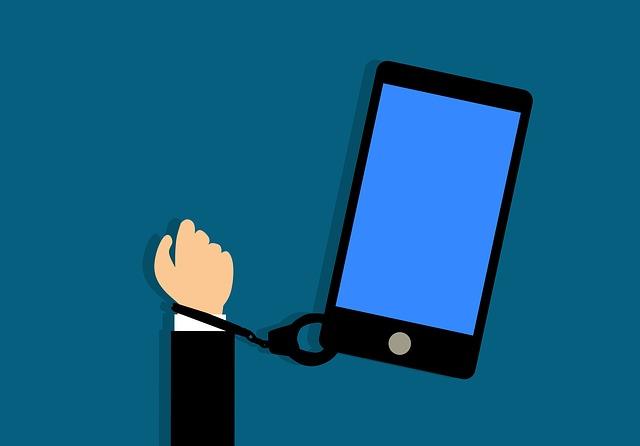 Un teléfono móvil aparece esposado a una mano.