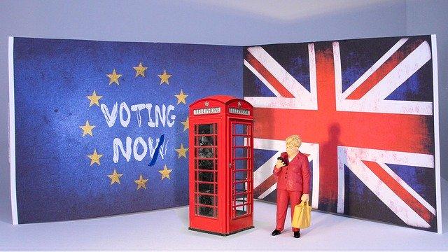 Una mujer mira su móvil tras el Brexit al lado de una cabina telefónica.