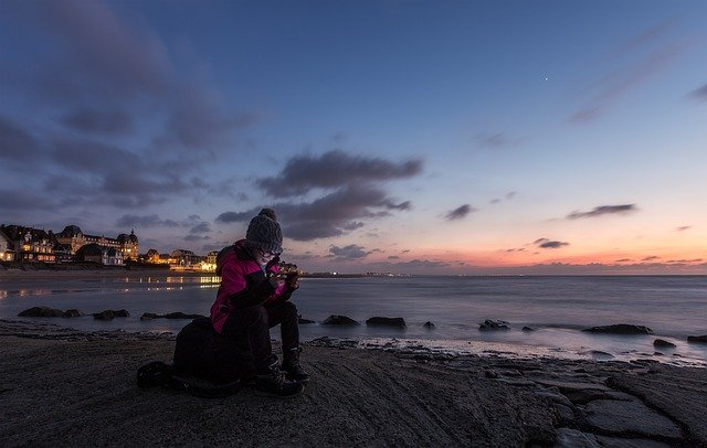 Una joven mira el teléfono en la playa